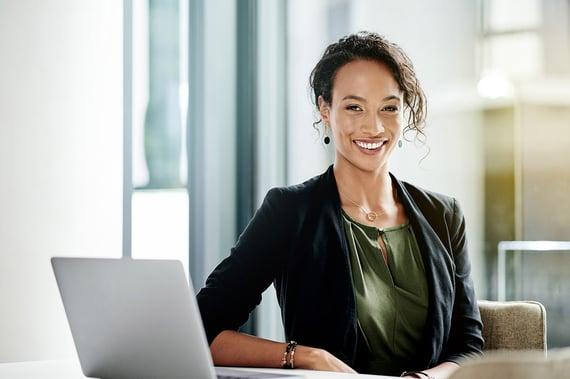 Kvinne på kontor som smiler til kamera