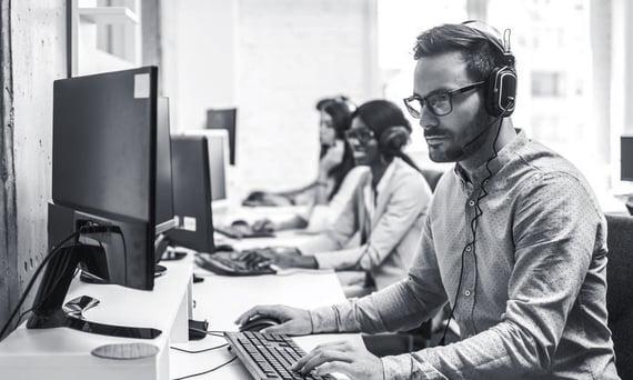 Mann med briller og headset jobber fokusert på datamaskin