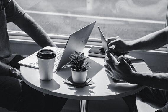 to personer jobber på laptop på kafé