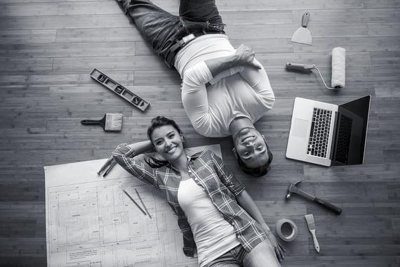 Kvinne og mann ligger på gulv og ser i kamera